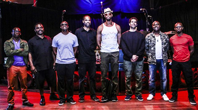 The eight members of Black Poet's Socieity in a line on stage