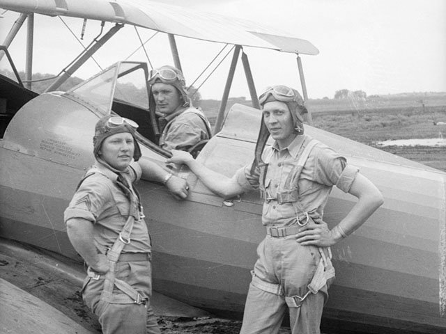At Truax during World War II: a U.S. Army Air Corps trainee in the cockpit of a biplane, with two flight instructors outside.